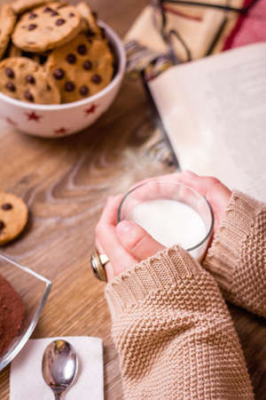 Closeup of female hands holding hot drink glass over a table with chocolate chip cookies on stars bowl photo