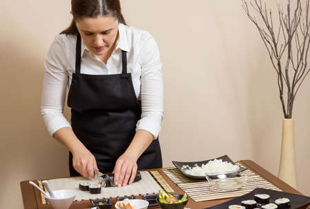 Portrait of woman chef cutting japanese sushi rolls with rice, avocado and shrimps on nori seaweed sheet photo