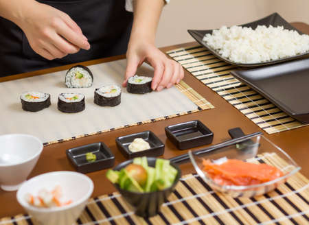 Closeup of woman chef putting japanese sushi rolls with rice, avocado and shrimps on nori seaweed sheet Stock Photo