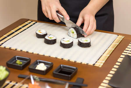 Closeup of woman chef cutting japanese sushi rolls with rice, avocado and shrimps on nori seaweed sheet photo