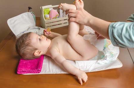 Mẹ thay tã của em bé đáng yêu với một bộ vệ sinh cho trẻ sơ sinh trên nền