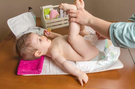 diaper changing table: Mother changing diaper of adorable baby with a hygiene set for babies on the background Stock Photo