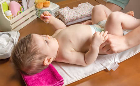 diaper changing: Mother changing diaper of adorable baby with a hygiene set for babies on the background Stock Photo