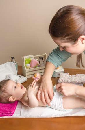 Mãe trocar a fralda do bebê adorável com um conjunto de higiene para bebês no fundo