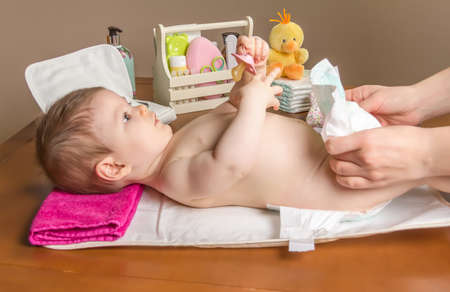 Mother changing diaper of adorable baby with a hygiene set for babies on the background photo