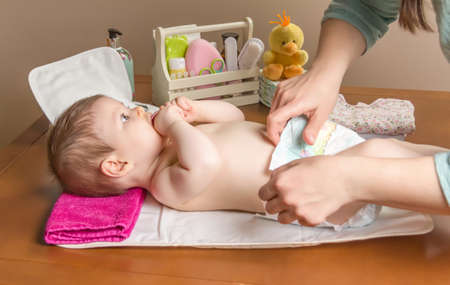 Mother changing diaper of adorable baby with a hygiene set for babies on the background Stockfoto