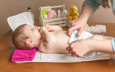 Mutterändernde Windel von adorable Baby mit einem Hygiene-Set für Kleinkinder auf dem Hintergrund Standard-Bild