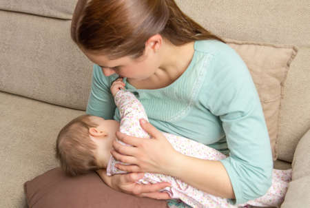 Genç annesi meme rahat bir ortamda evde bebeğini besleme