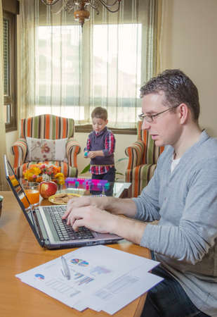 hard look: Father working hard in home office with notebook and his boring son playing on the background