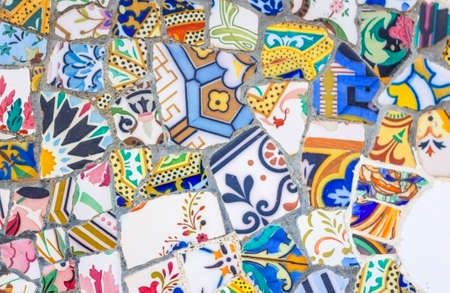 Famous colorful ceramic mosaics detail, designed by Antonio Gaudi and better known as  trencadis   Located in the park Guell of Barcelona, Spain Stock Photo