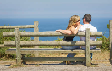Back view of beautiful love couple sitting outdoors on a bench looking the sea and sky in background photo