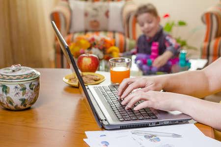 여자의 세부 노트북 및 백그라운드에서 재생하는 소년에서 작성 홈 오피스 개념