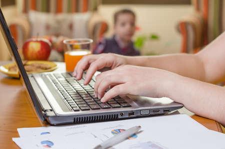 madre trabajando: Detalle de manos de una mujer escribiendo en el cuaderno y el niño jugando en el concepto de Ministerio del Interior de fondo Foto de archivo