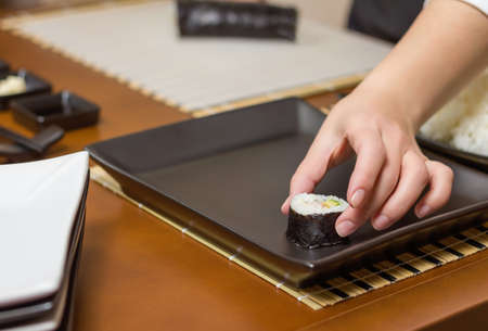 Closeup of woman chef placing japanese sushi rolls with rice, avocado and shrimps on nori seaweed sheet over a black rectangular tray