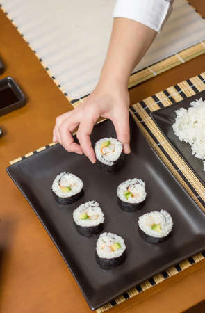 placing: Closeup of woman chef placing japanese sushi rolls with rice, avocado and shrimps on nori seaweed sheet over a black rectangular tray