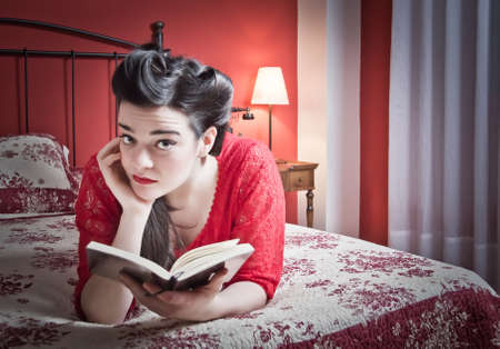 Portrait of beautiful fashion young girl with white makeup and wearing retro red dress reading a book lying down in the bed  Classic vintage style concept  photo