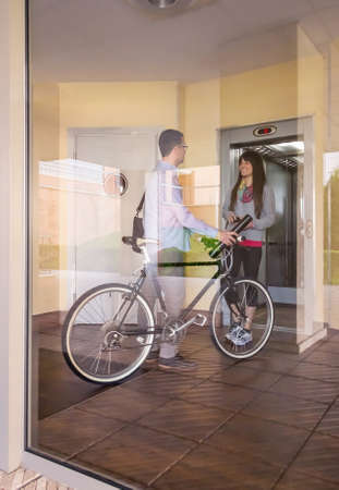 Handsome casual business man and beautiful girl with sportswear speaking in a office hall entrance behind the glass wall photo