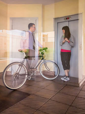 Handsome casual business man and beautiful girl with sportswear waving in a office hall entrance behind the glass wall photo