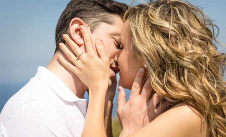 enamorados besandose: Pares apasionados hermoso amor beso al aire libre en un día de verano sobre fondo de naturaleza