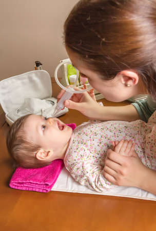 mucus: Mother cleaning mucus catarrh of adorable baby with a nasal aspirator