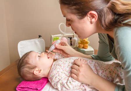 Mãe limpeza muco catarro do bebê adorável com um aspirador nasal