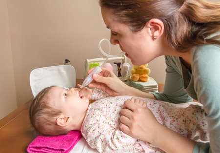 Madre limpiar la mucosidad catarro del bebé adorable con un aspirador nasal