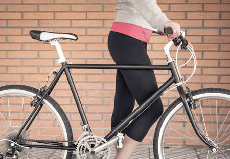 Closeup of customized fixie bike and beautiful young sportive woman over a orange brick wall on the background photo