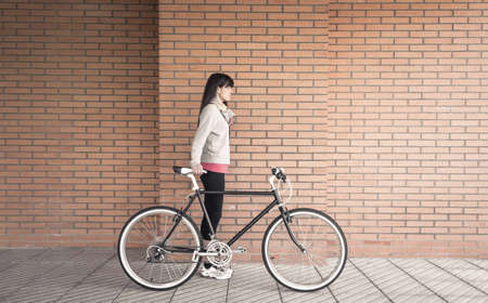 Beautiful young sportive woman posing with custom fixie bike over a orange brick wall on the background photo
