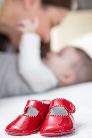 quiet baby: Closeup of baby red patent leather shoes over a bed and babe playing with her mother on the background