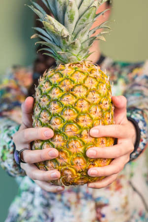 Colorful fashion girl portrait holding a pineapple between her hands over green background photo