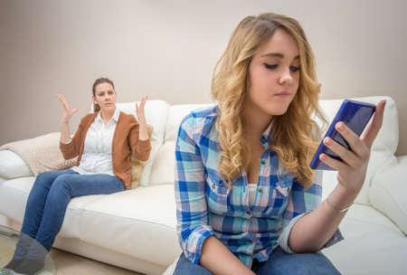 スマート フォンでメッセージを探していると新技術によって彼女の猛烈な母悪い家族のコミュニケーション概念を無視する 10 代の娘