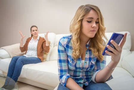 Teenage daughter looking messages in a smartphone and ignoring her furious mother  Bad family communication concept by new technologies