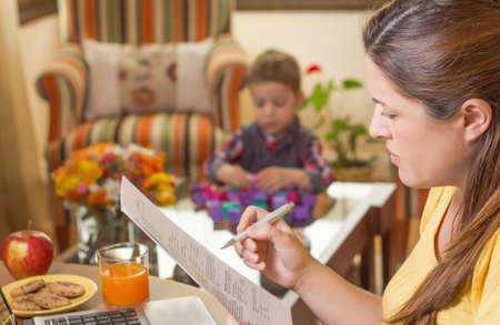 madre trabajando: Madre embarazada leer documentos de negocios en una oficina en casa y su hijo aburrido jugando en el fondo