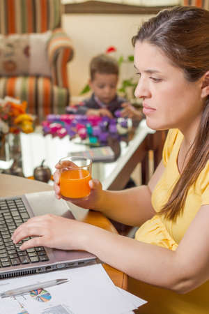 Pregnant mother working in home office with notebook and his boring son playing on the background photo