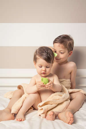 Portrait of sweet boy combing little girl under the towel playing with toy over a bed after bath photo