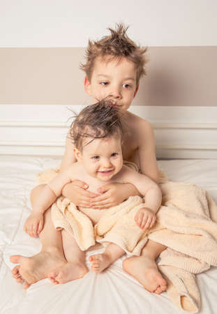 Portrait of sweet boy and little girl with wet hair under the towels sitting in a bed after bath photo