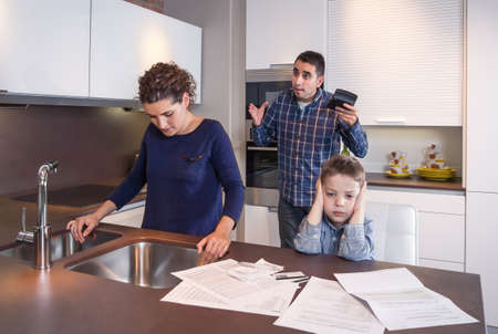 Sad son and worried mother suffering while furious father scream in a home kitchen by economic difficulties  Family problems concept  Archivio Fotografico