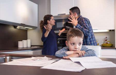 Грустный ребенок страдания и его родители, имеющие жесткий разговор в домашней кухне по пару трудности семейных проблем концепции