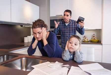 male parent: Sad son and worried mother suffering while furious father scream in a home kitchen by economic difficulties  Family problems concept  Stock Photo
