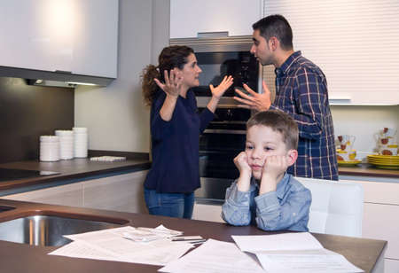 problemas familiares: Niño triste sufrimiento y sus padres tienen discusión dura en la cocina de su casa por las dificultades de pareja Problemas familiares concepto