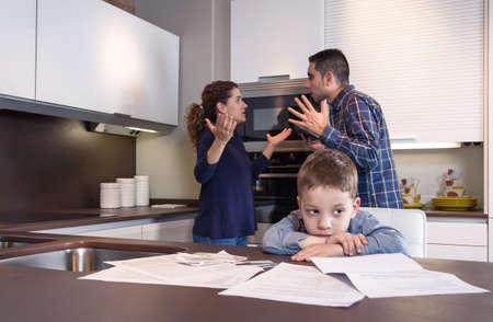 Sad dítě utrpení a jeho rodiče mají pevný diskusi v domácí kuchyni o pár problémů s rodinnými problémy koncepce