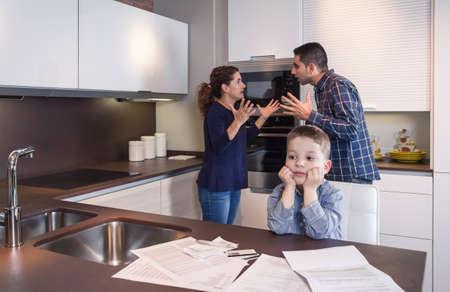 problemas familiares: Ni�o triste sufrimiento y sus padres tienen discusi�n dura en la cocina de su casa por las dificultades de pareja Problemas familiares concepto