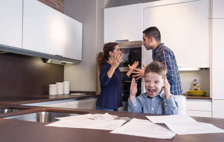 family problems: Furious child screaming and his parents having hard discussion in a home kitchen by couple difficulties  Family problems concept  Stock Photo