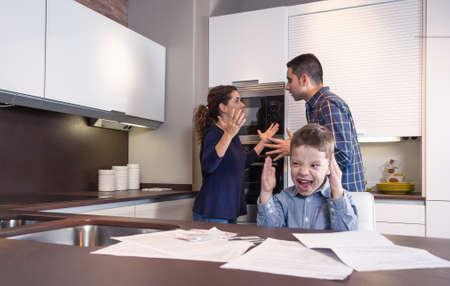 problemas familiares: Ni�o furiosa que grita y sus padres tienen discusi�n dura en la cocina de su casa por las dificultades de pareja Problemas familiares concepto
