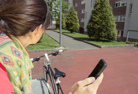 Beautiful young sportive woman with custom fixie bike looking smartphone sitting on park bench in a sunny summer day  Soft and warm tones  photo