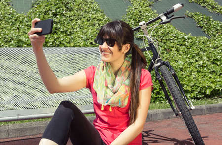 Closeup of beautiful young sportive woman with custom fixie bike looking her smartphone in a sunny summer day  Soft and warm tones  photo
