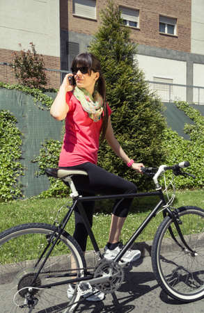 Beautiful young sportive woman with custom fixie bike calling by smartphone in a sunny summer day on the city  Soft and warm tones  photo