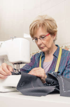 Senior seamstress woman working with clothing item on a sewing machine photo
