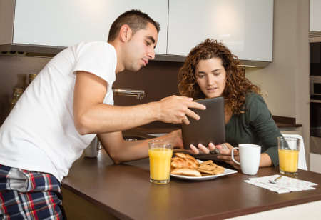 Happy young couple looking a digital tablet while having breakfast at home kitchen photo