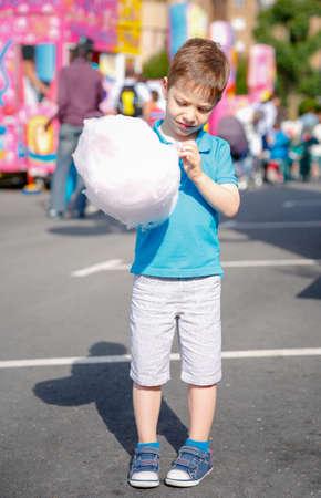 algodon de azucar: Retrato de niño lindo que come el caramelo de algodón sobre un festival justo el verano de fondo Foto de archivo